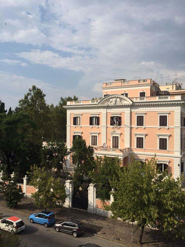 ภาพตัวอาคารสีชมพูอมส้มหรือสีแซลมอนของสถานเอกอัครราชทูต